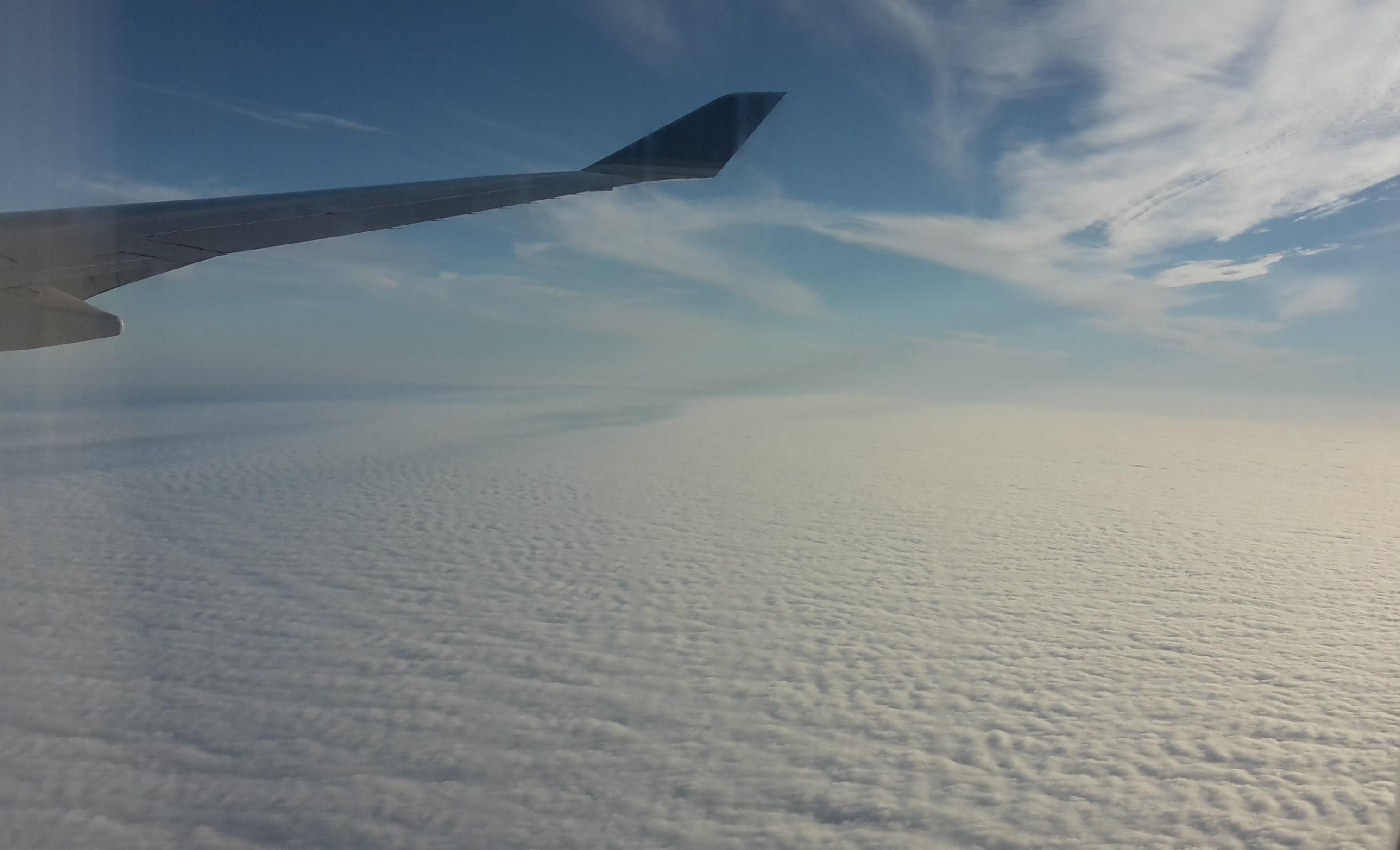 Blick aus dem Flugzeugfenster, zu sehen ist ein Wolkenmeer
